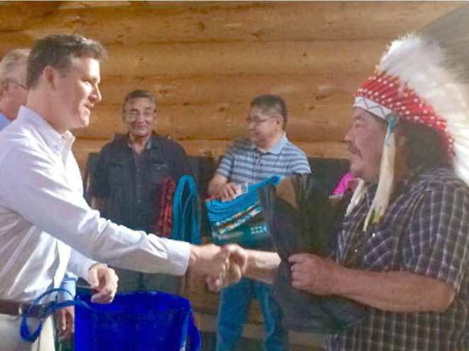 Grand Chief Warren White and Energy East Pipeline President François Poirier shake hands during a traditional ceremony in the sacred roundhouse of the Wauzhushk Onigum community, near Kenora, Ont.